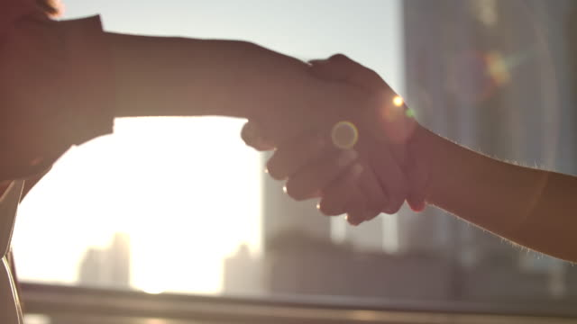 slo mo close-up handshake mit sonnenlicht in der stadt - filmtechnik bildkomposition und technik stock-videos und b-roll-filmmaterial