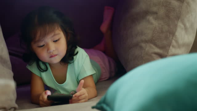 close-up happy toddler girl watching cartoon on mobile phone. digital native. addict - digital native stock videos & royalty-free footage