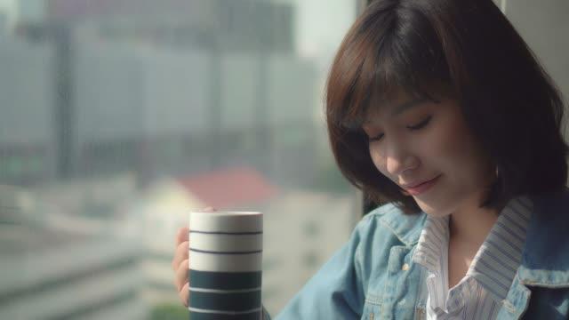 vídeos y material grabado en eventos de stock de close-up feliz mujer joven sonríe y utiliza el teléfono inteligente - té bebida caliente