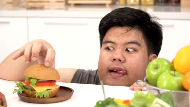 close-up head shot: thai overweight man prefers unhealthy foods such as hamburger more than salad or fruit - hamburger stock videos & royalty-free footage