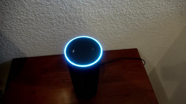 closeup high angle view of an amazon echo smart speaker on a small wooden table in a smart home setting speaker illuminating in blue color indicating... - högtalare bildbanksvideor och videomaterial från bakom kulisserna