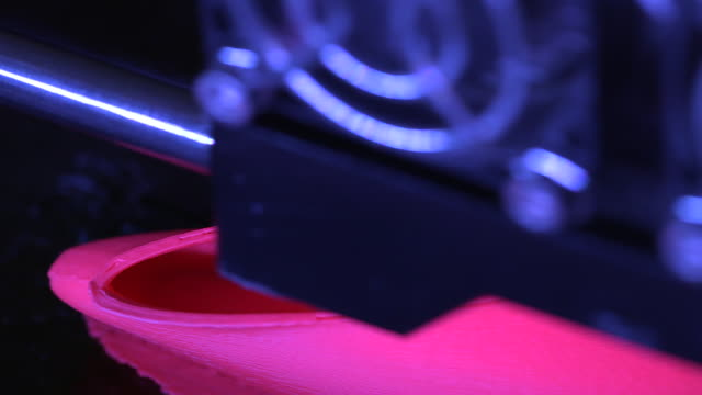 Close-up high-angle shot showing the arm of a 3D printer as a bright pink object is printed, UK.