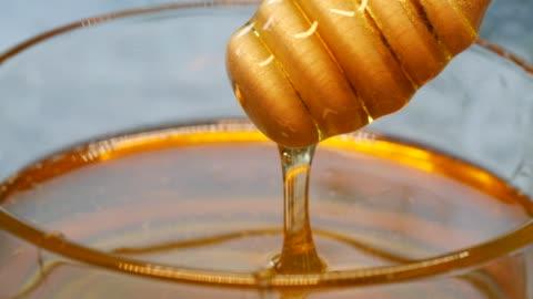 vídeos y material grabado en eventos de stock de miel de primer plano que fluye de la cena de madera - cucharón