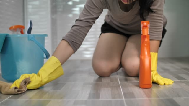close-up housewife in yellow gloves cleaning on floor with spray - pavimento video stock e b–roll
