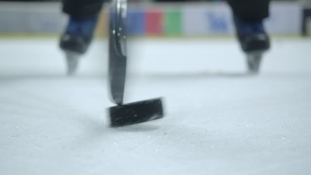 4k close-up ice hockey players are practicing using hockey sticks to dribble the puck. ice hockey ice rink - hitting stock videos & royalty-free footage