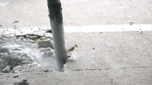 Close-up Presslufthammer Bagger Bohren den Betonboden in Zeitlupe erschossen.