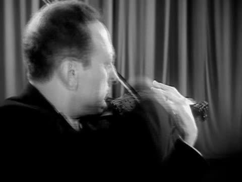 Closeup Jascha Heifetz playing violin during performance/ USA