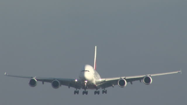 closeup landing shot of emirates a380 at heathrow taken from side of runway initial approach is viewed faceon with no noticeable branding or livery... - landing touching down stock videos & royalty-free footage