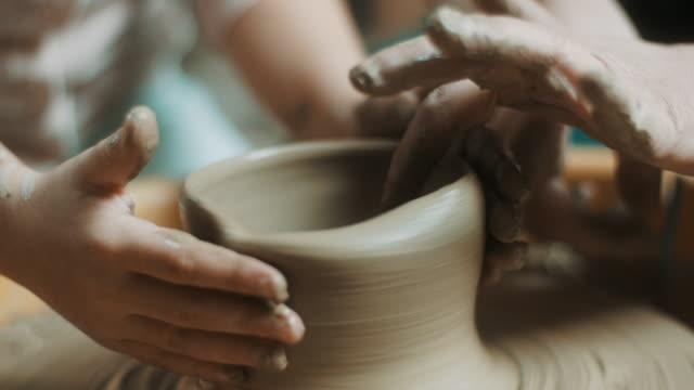 拡大すると、小さな女の子のアトリエで陶器のホイールを使用して - 陶器点の映像素材/bロール