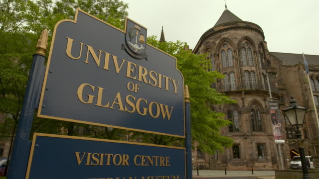 close-up lockdown shot of blue signboard near university building in city - glasgow, scotland - capital letter stock videos & royalty-free footage