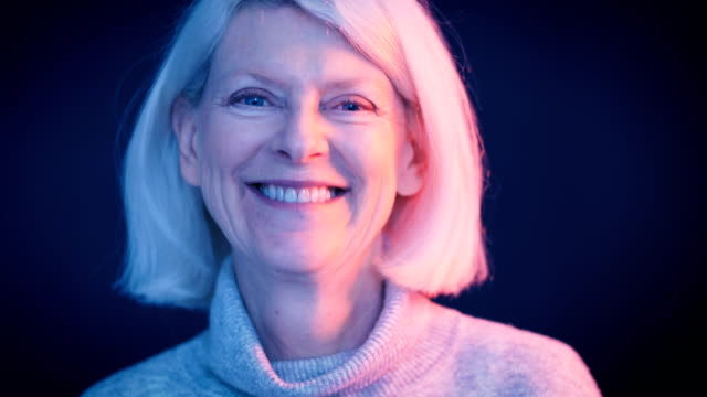 close-up lockdown shot of senior businesswoman smiling against gray background - grey hair stock videos and b-roll footage