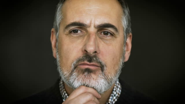 Close-up lockdown shot of thoughtful mature businessman over gray background