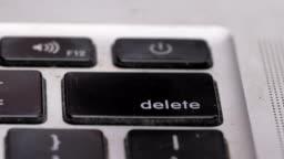 closeup macro finger franticly presses delete button computer