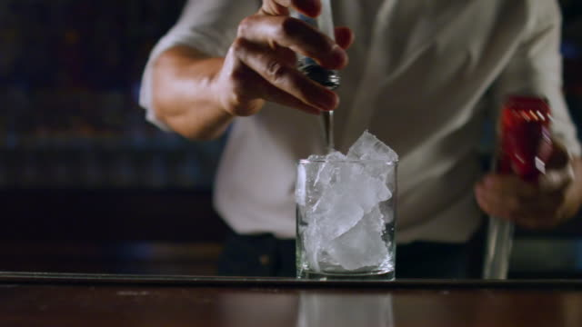 close-up: male bartender making a drink (shot on red) - happy hour video stock e b–roll