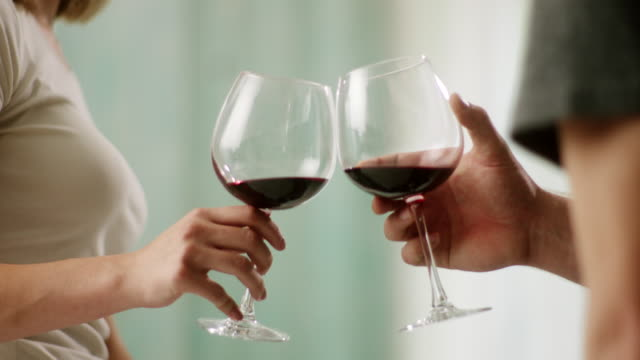 close-up, man and woman toasting with red wine - bicchiere da vino video stock e b–roll