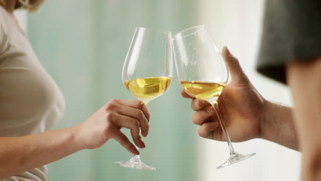Close-up, man and woman toasting with white wine