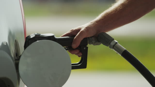 closeup man finishes pumping gas, removes nozzle from the vehicles gas tank. - only mature men stock videos & royalty-free footage
