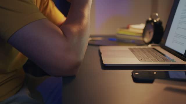 primo passo mano dell'uomo che lavora a casa digitando sul computer portatile di notte - scadenza video stock e b–roll