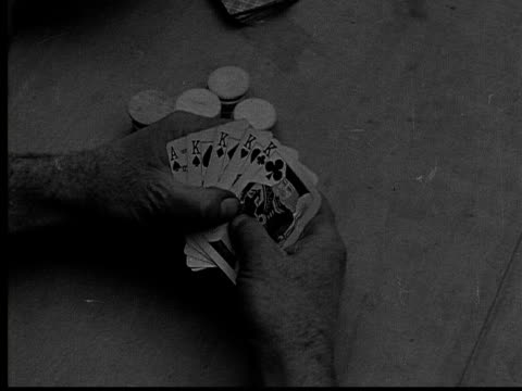 vídeos de stock, filmes e b-roll de 1915 b/w close-up man holding poker hand with four king cards and an ace card  - pôquer