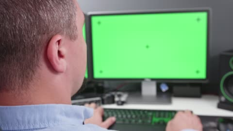 fpv close-up man in office working on dual monitor computer with green screen for chroma key - two objects stock videos & royalty-free footage