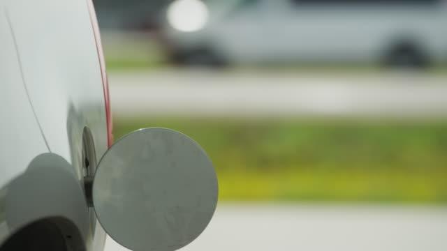 vídeos de stock e filmes b-roll de closeup man inserts a gas nozzle into a car's gas tank at a gas station. - combustível fóssil