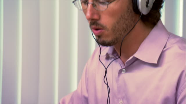 close-up man listening to headphones in office - desktop pc stock-videos und b-roll-filmmaterial