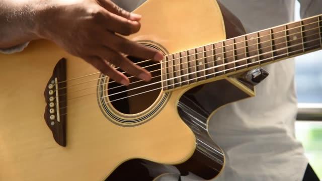 vidéos et rushes de gros plan homme jouer de la guitare - guitariste