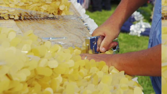 closeup man staples chicken wire and yellow decorations to a parade float he is constructing. - ホッチキス点の映像素材/bロール