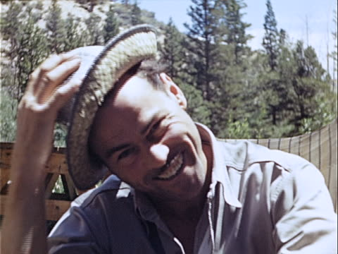 1949 Close-up Man tipping straw hat and smiling outdoors near picnic table and forest / USA