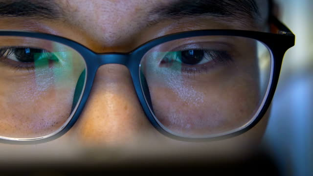 Close-up man with eyeglasses using mobile phone