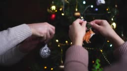 Close-up man's and woman's decorate the Christmas tree in slow motion