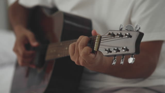 close-up  : man's hands finger picking and playing guitar - bed furniture stock videos & royalty-free footage