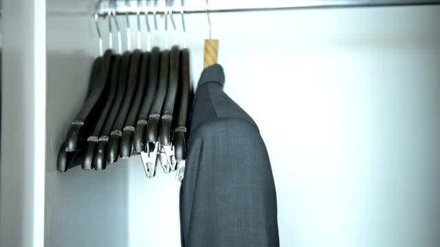 Closeup man's hands looking through clothes rack