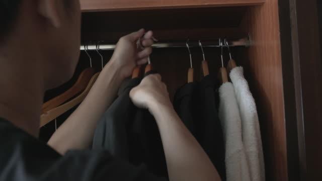vídeos y material grabado en eventos de stock de primer plano de manos del hombre mirando a través de la barra para colgar la ropa - colgador
