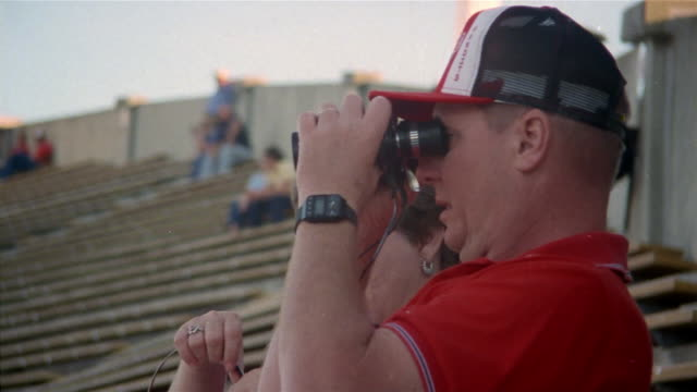 stockvideo's en b-roll-footage met 1985 close-up mature football fans looking through binoculars and putting on headphones during game / tampa, florida, usa  - verrekijker