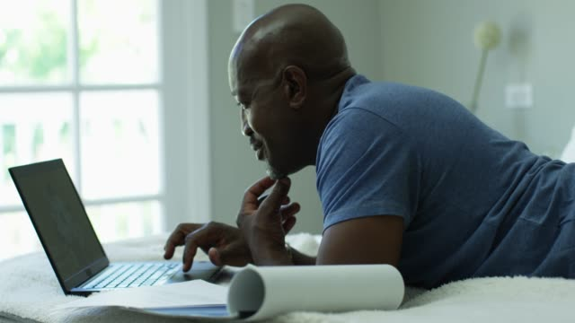 close-up, mature man smiles while using laptop in bed - hot desking stock videos & royalty-free footage