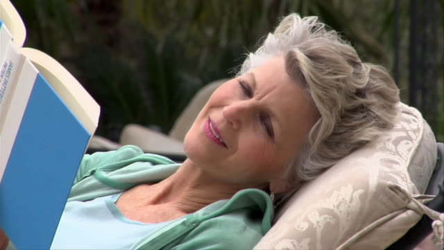 vidéos et rushes de close-up mature woman reading book and reclining in lounge chair on patio/ san antonio, texas, usa - femmes d'âge mûr