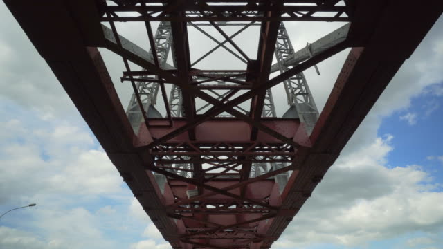 close-up: metallic girder bridge in city against cloudy sky - novosibirsk, russia - 桁橋点の映像素材/bロール