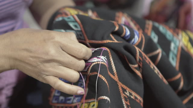 close-up midsection of woman stitching black fabric for sale at street night market - luang prabang, laos - sewing stock videos & royalty-free footage