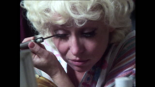 close-up mirror shot of barbara windsor putting on mascara. camera pulls out showing barbara applying face powder in a mirror; 1981. - only women stock videos & royalty-free footage