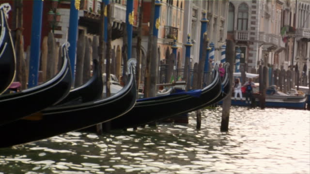 vídeos de stock e filmes b-roll de close-up. moored gondolas floating in a canal with tourists in the background in venice, italy. - embarcação comercial