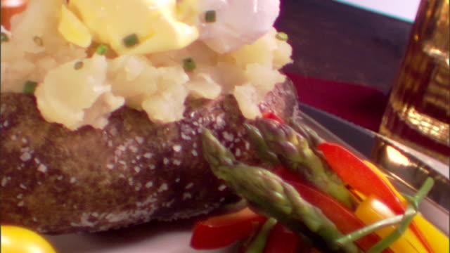 vídeos de stock e filmes b-roll de close-up move down from the potato to the steak on a plate. - cortado em filete