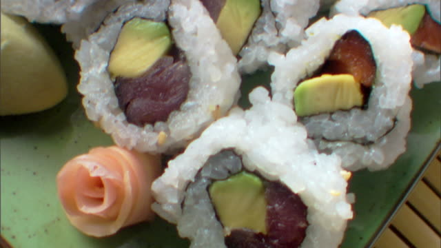 close-up move over a plate of rolled sushi to a cup of steaming sake. - wasabi sauce stock videos and b-roll footage