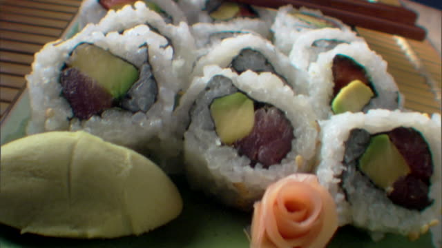 close-up move tracking over a plate of rolled sushi to a cup of sake. - wasabi sauce stock videos and b-roll footage