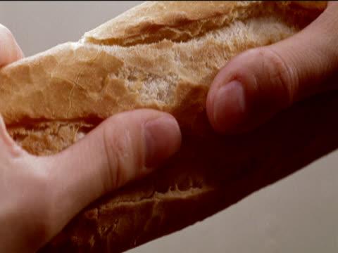 stockvideo's en b-roll-footage met close-up of a baguette being broken in half - onbekend geslacht