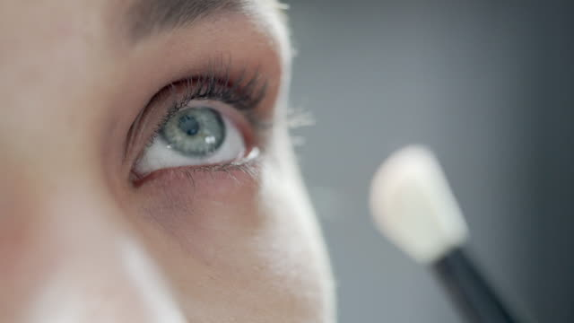 a close-up of a beautician applying eyeshadow, with a brush to a models eyelids - make up stock videos & royalty-free footage