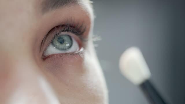 モデルのまぶたにブラシで、アイシャドウを適用する美容師のクローズアップ - メイクアップアーティスト点の映像素材/bロール