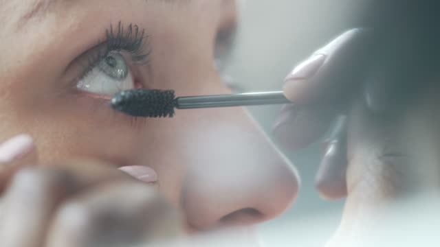 a close-up of a beautician applying mascara to a models eyelashes - mascara stock videos & royalty-free footage