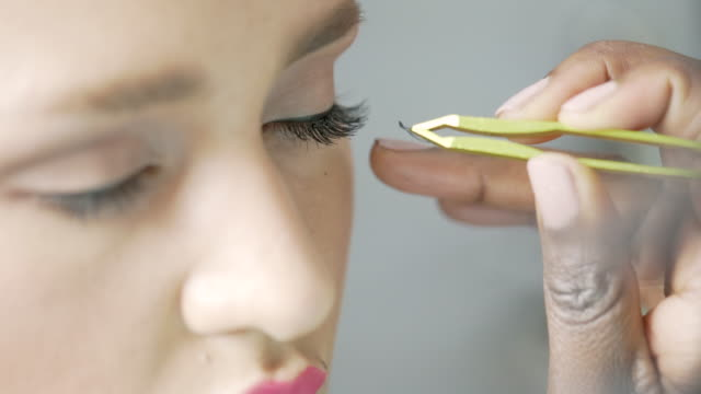モデルの目に個々のまつげを慎重に適用する美容師のクローズアップ - 美容専門家点の映像素材/bロール