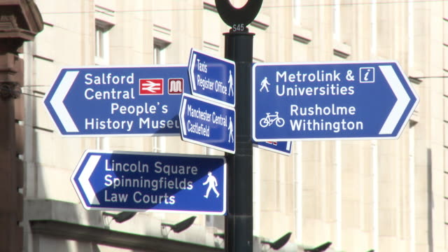 close-up of a blue signpost in central manchester indicating rusholme, withington, salford, lincoln square, spinningfields, the people's history museum and the law courts, uk. - manchester england stock videos & royalty-free footage